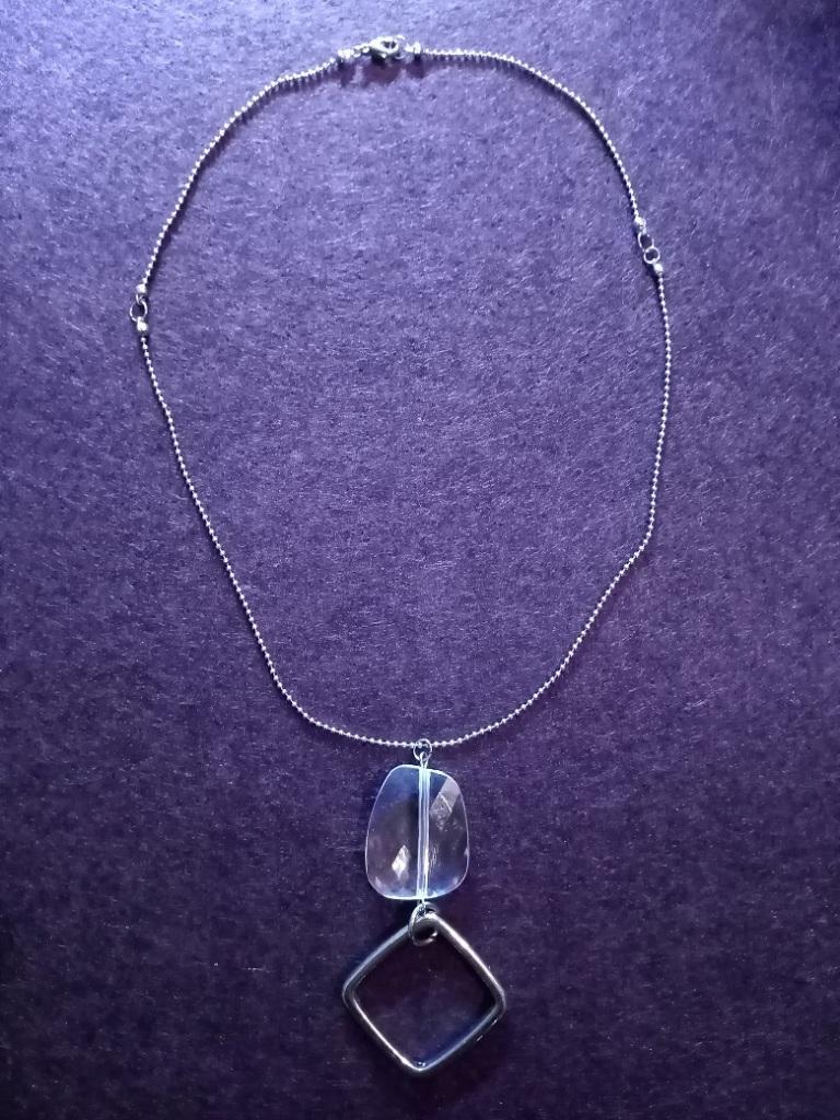 Collier et pendentif PURE CLARTE composé d'une chaîne-bille en métal argenté, d'un fermoir et d'un pendentif perle transparent et d'un losange.